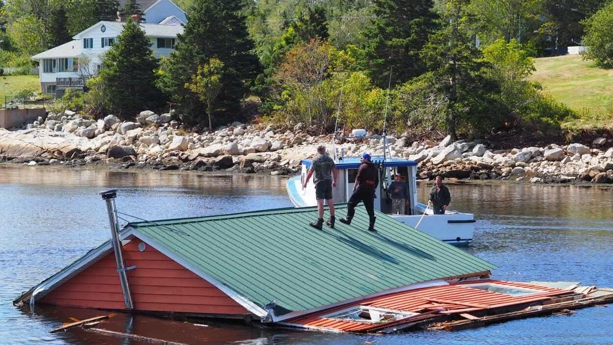 Des hommes se tiennent debout sur le toit d'une maison submergée et remorquée par un bateau.