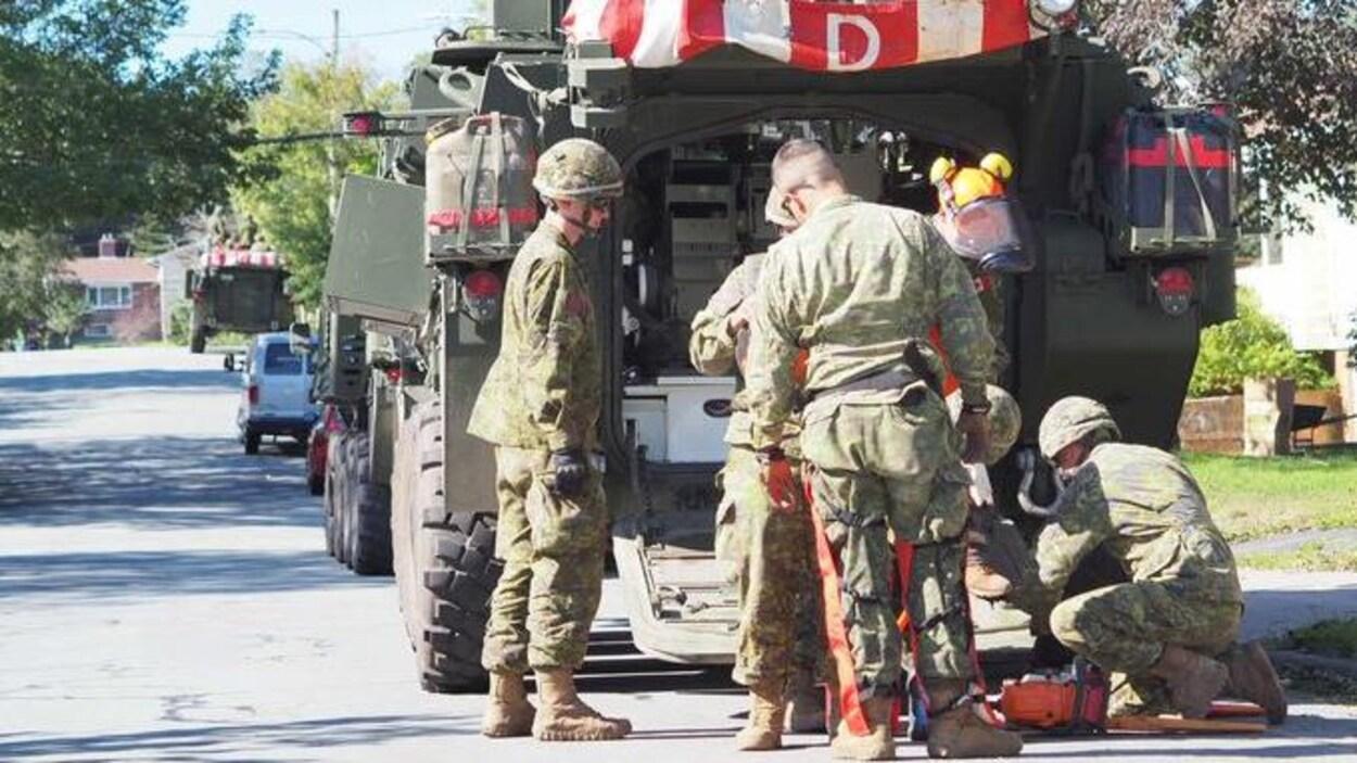 Des soldats sortent de l'équipement de leur véhicule blindé garé le long d'une rue.