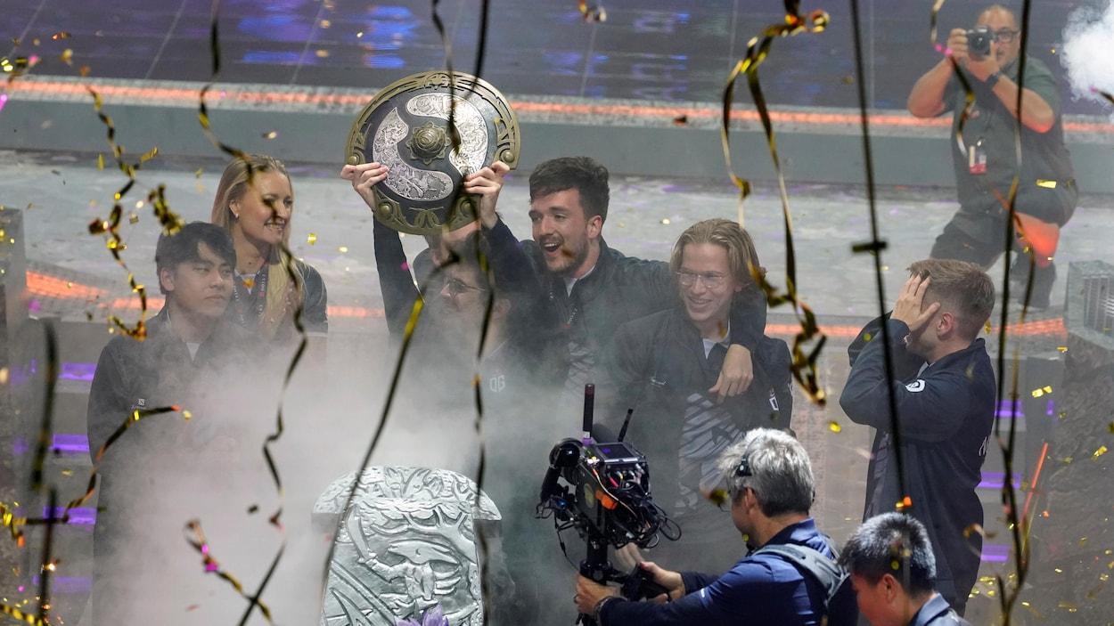 Les joueurs qui ont remporté le tounoi de Dota 2 the International célèbrent leur victoire en tenant un trophée.