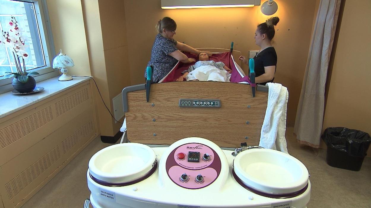 Deux préposés se pratiquent à utiliser une douche dans un lit avec un mannequin.