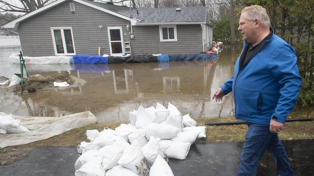 Un homme marchant près d'une zone inondée par une crue printanière.