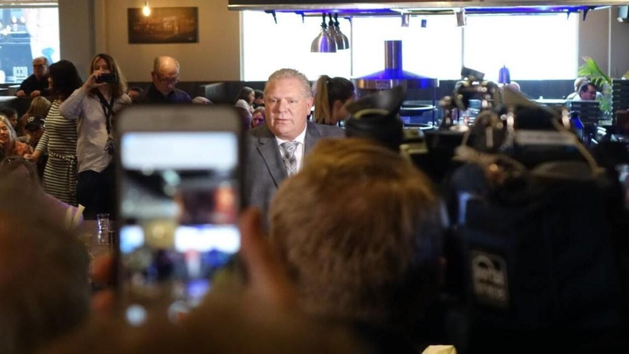 Doug Ford dans un restaurant entouré de plusieurs militants qui le photographient.
