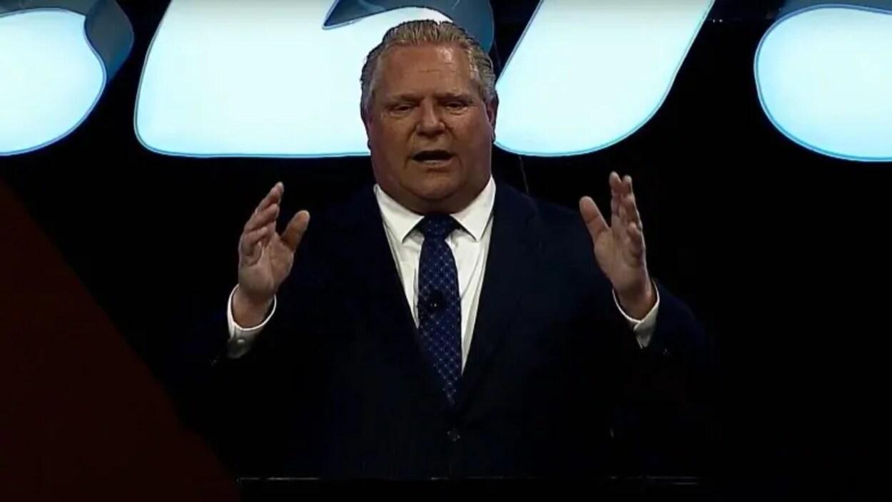 Photo d'un homme en complet qui tient les mains levées dans les airs alors qu'il parle.