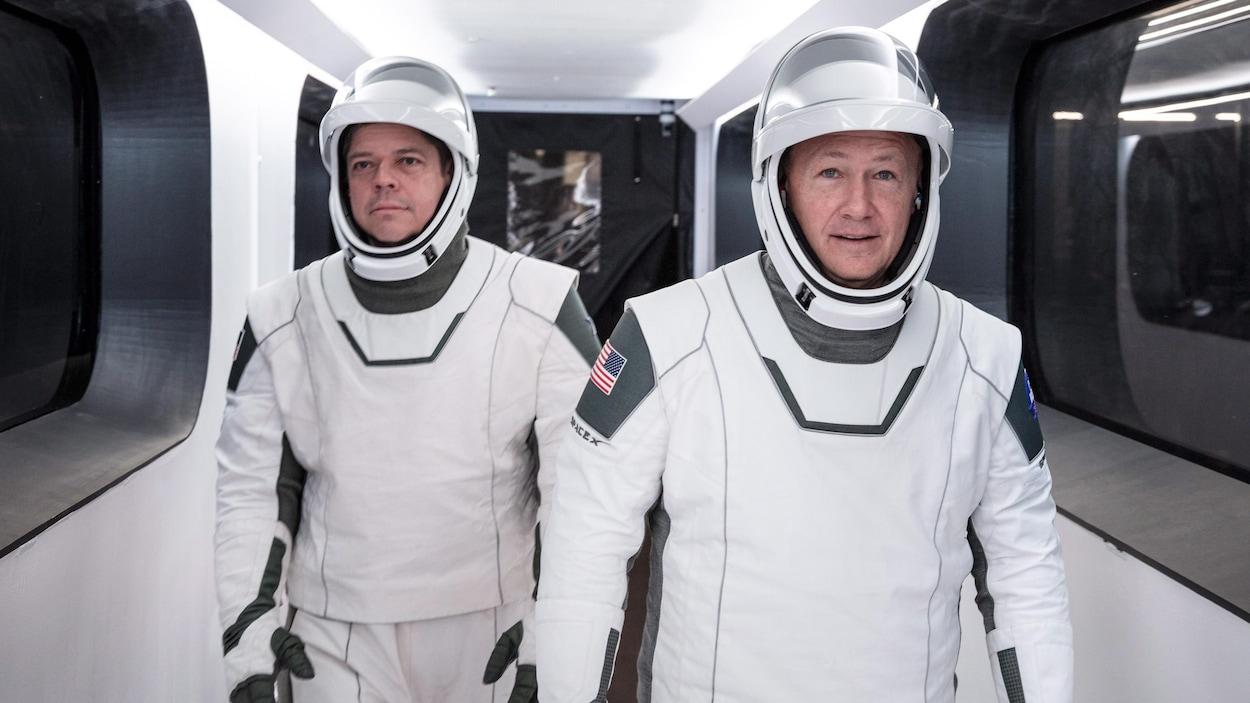 Les deux hommes marchent vêtus de leur combinaison d'astronaute.