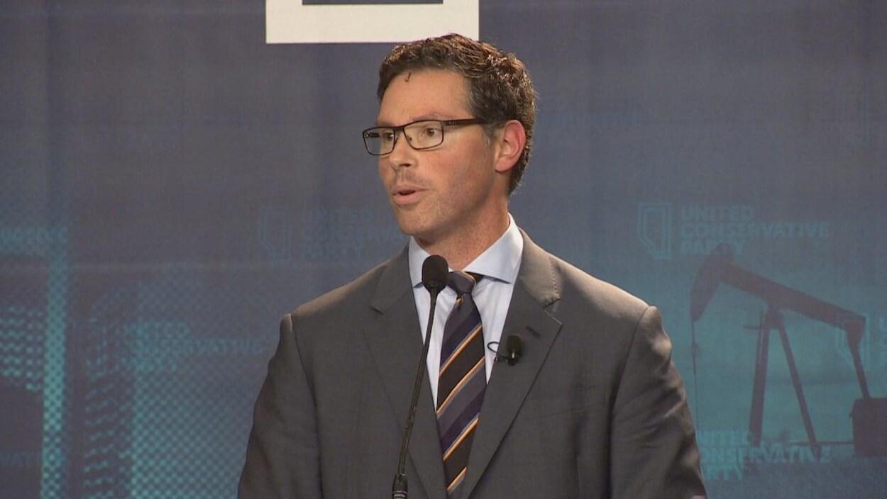 Le ministre de la Justice, Doug Schweitzer, porte des lunettes et un costume-cravate pendant qu'il parle devant un micro.