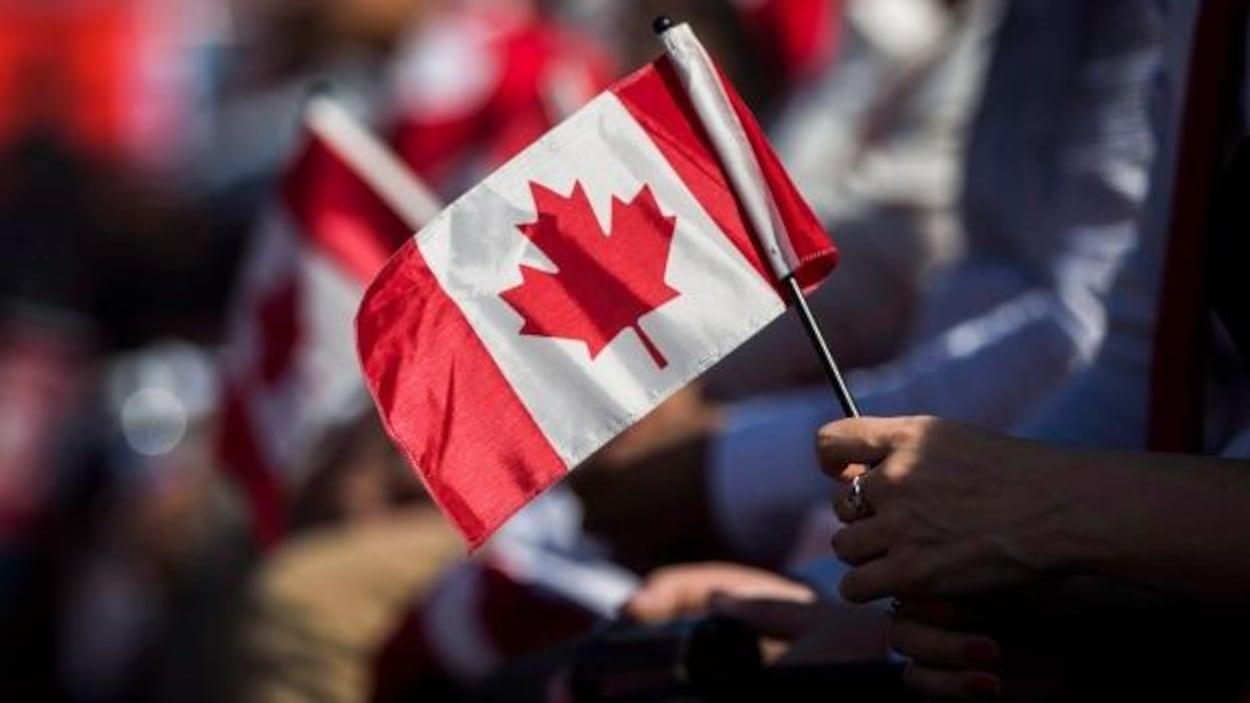 Une femme tient un drapeau canadien dans sa main.