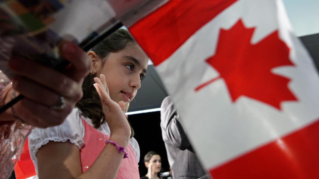 Une petit fille prête serment dans une cérémonie d'octroi de la citoyenneté canadienne, avec un drapeau canadien à l'avant-plan.