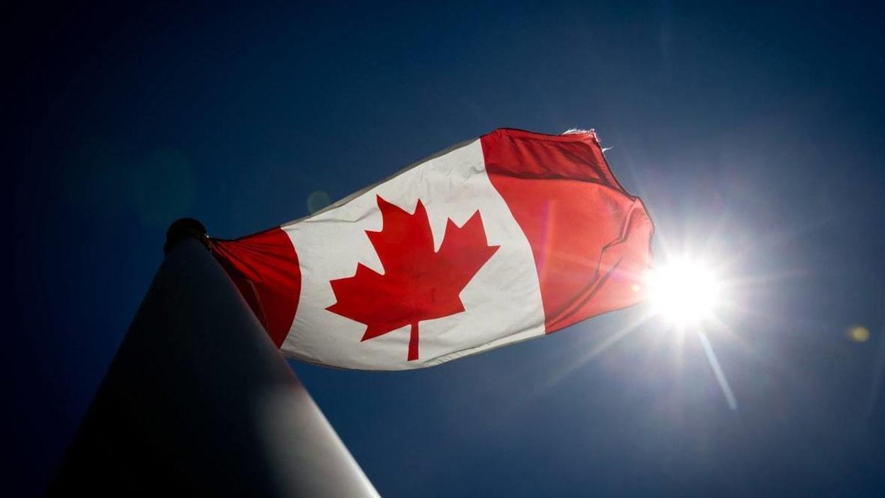 Le drapeau du Canada vu par en dessous avec dans le coin le soleil.