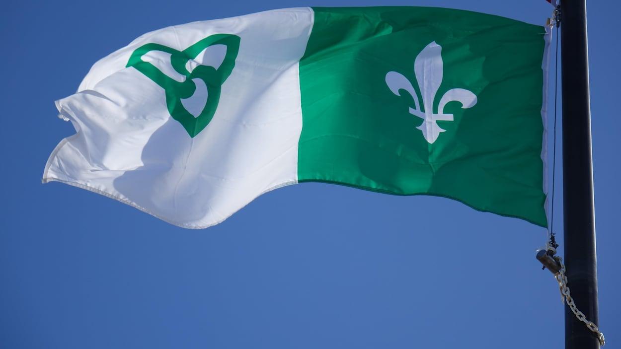 Le drapeau blanc et vert flotte au vent.