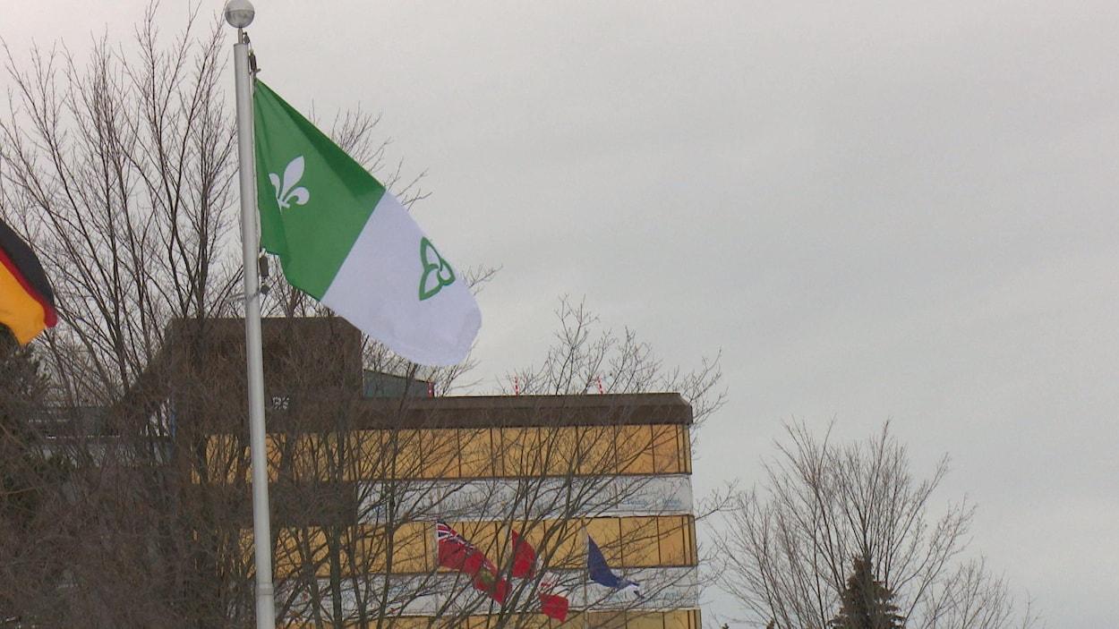 Un drapeau flotte au vent devant un édifice gouvernemental à multiples étages.