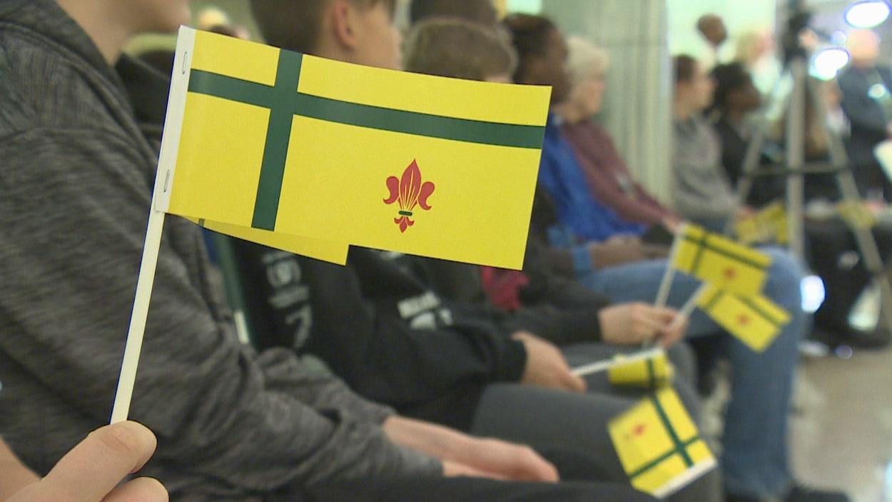 Un jeune tient un petit drapeau fransaskois dans ses mains.