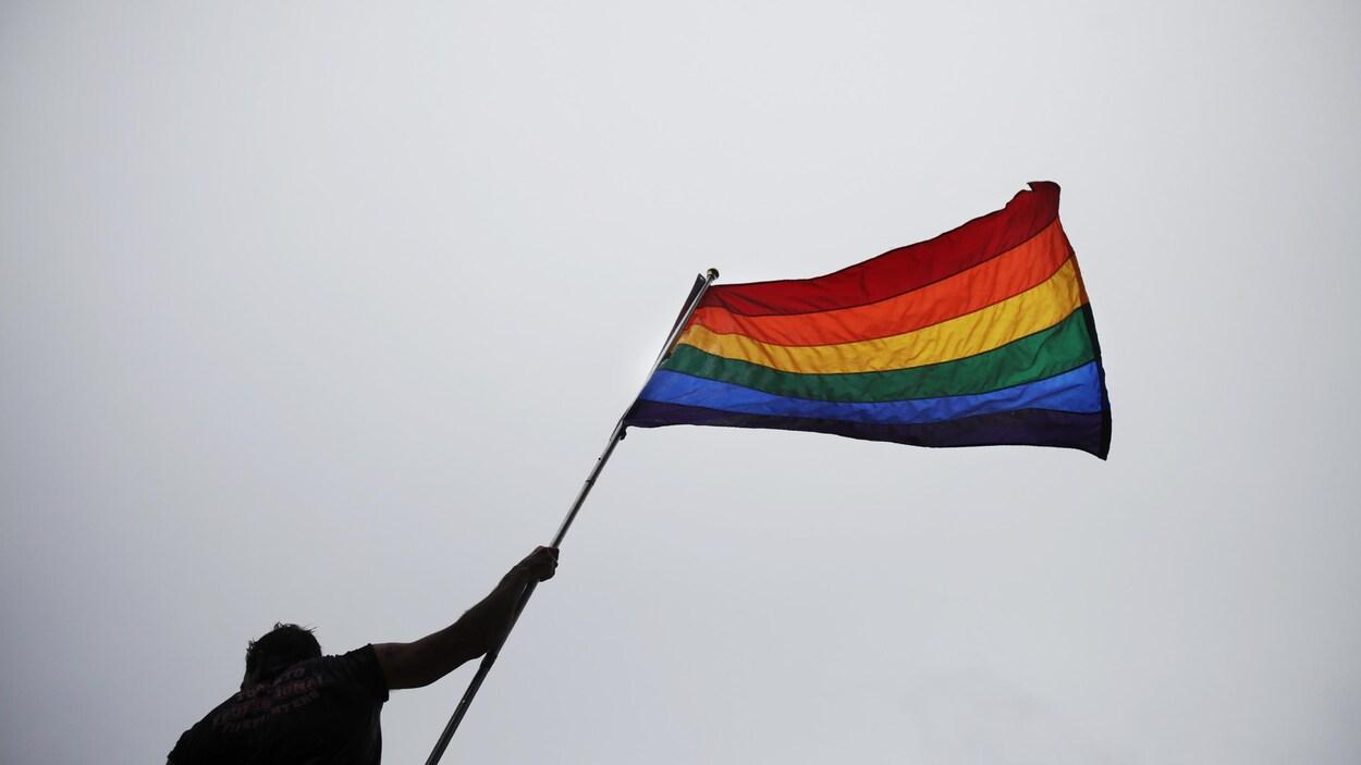 Un homme tient dans sa main droite un drapeau ayant aux couleurs de l'arc-en-ciel. La photo a été prise en contre-plongée, c'est-à-dire que l'on voit de plus bas l'homme et le drapeau, comme si on levait la tête pour les regarder.