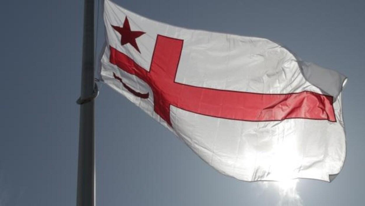 Le drapeau mi'kmaq, blanc avec une croix rouge, une étoile et un croissant de lune rouge.