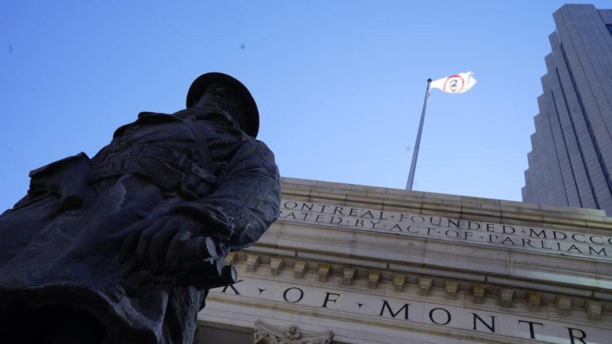 Un drapeau blanc avec un cercle rouge flotte au-dessus d'un bâtiment avec des colonnes.