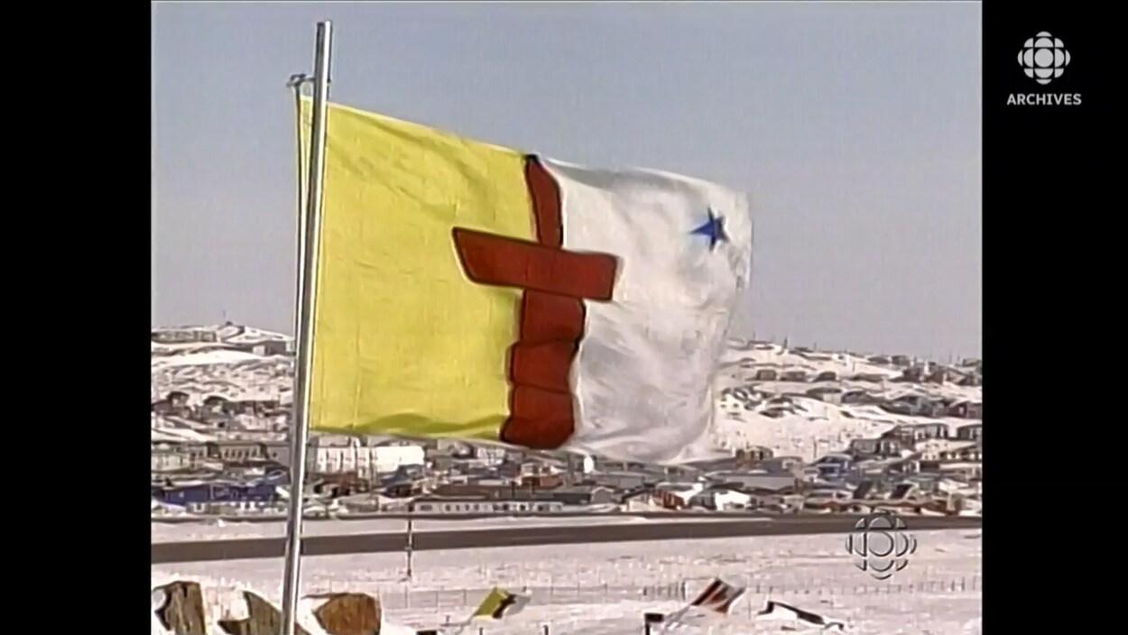 Le drapeau du Nunavut orné en son centre d'un inuksuk flottant au vent.