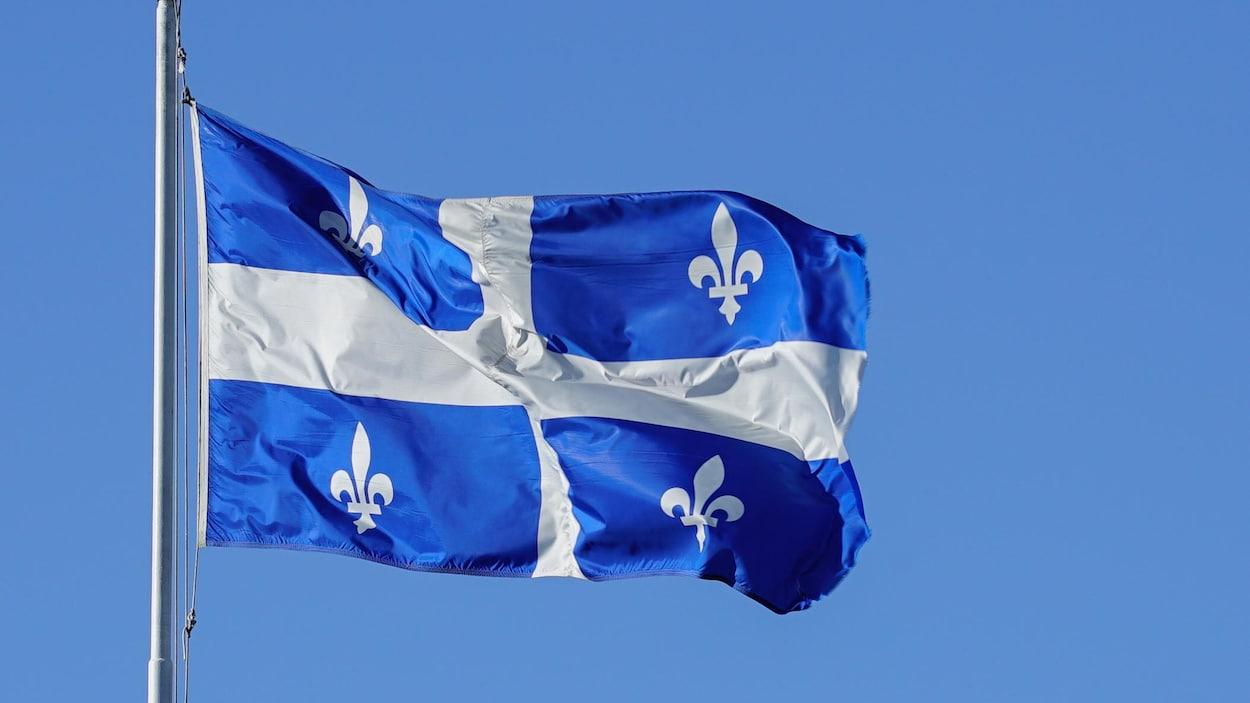 Le drapeau du Québec, au vent, sur un mât.