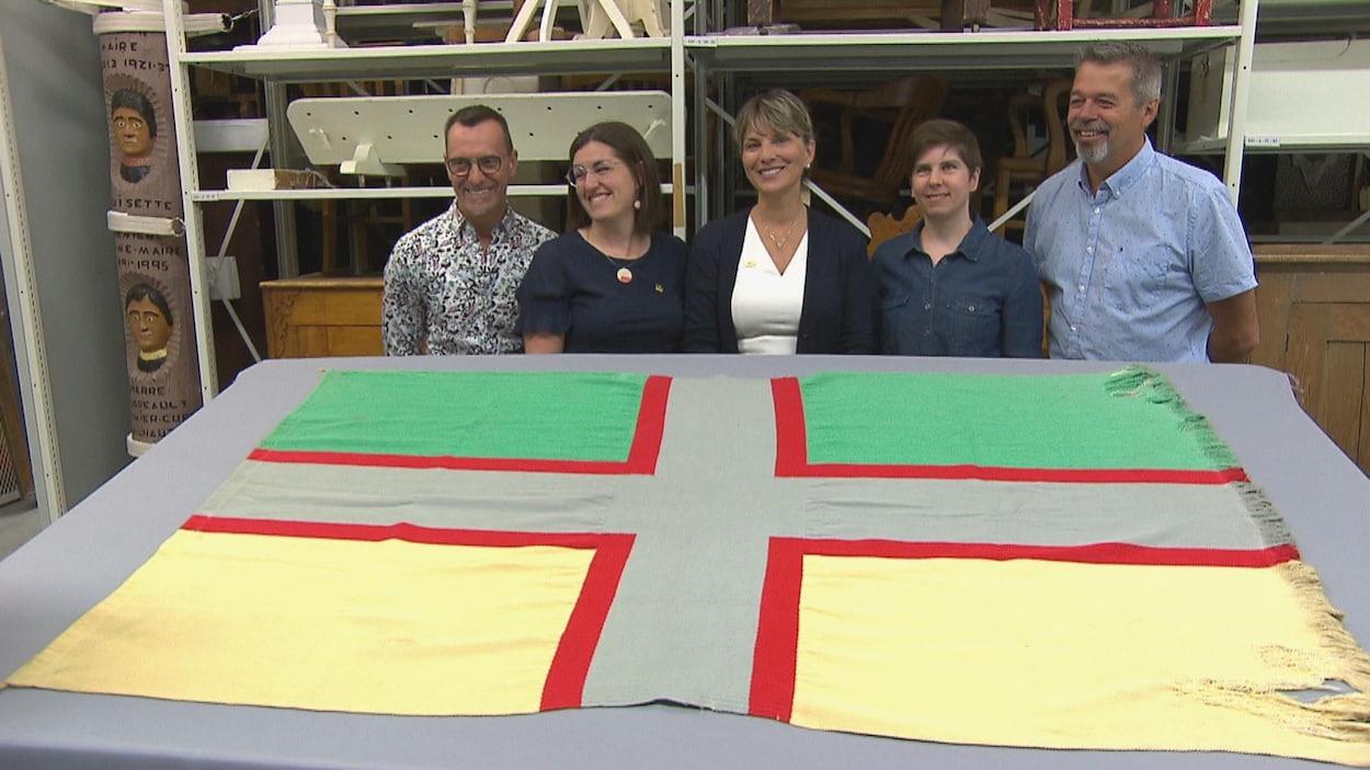Josée Néron et des représentants de la Pulperie derrière le drapeau du Saguenay-Lac-Saint-Jean