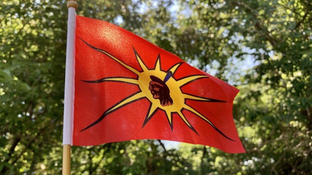 Le drapeau, sur lequel se trouve la tête d'un guerrier mohawk, flotte devant des arbres.