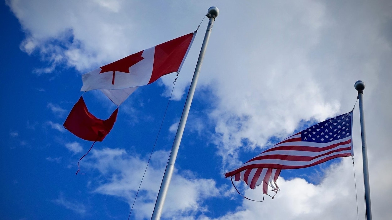 Des drapeaux canadien et américain endommagés flottent à Morrisburg.