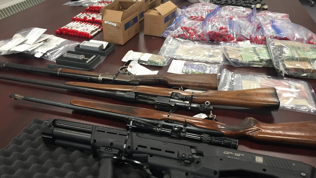 Du cannabis, de la cocaïne, de l'argent comptant, trois carabines et un fusil de chasse sont sur une table.
