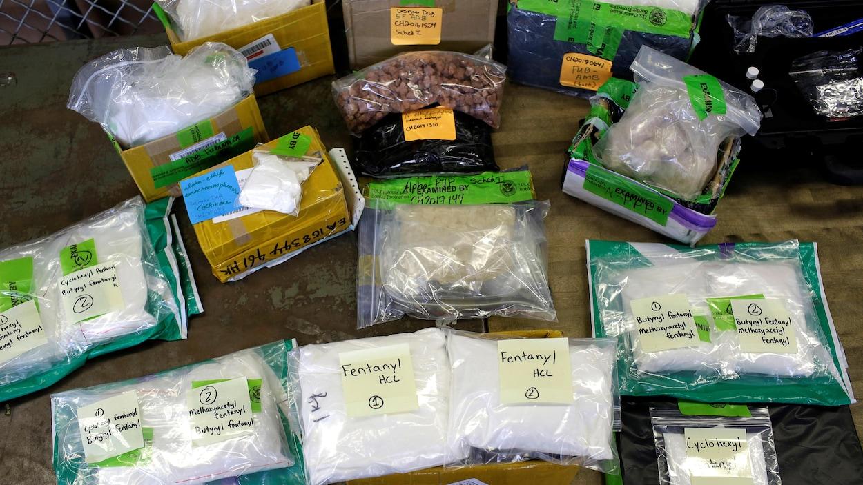 Plusieurs emballages de plastique contenant du fentanyl sont présentés sur une table en bois après avoir été saisis par les autorités.