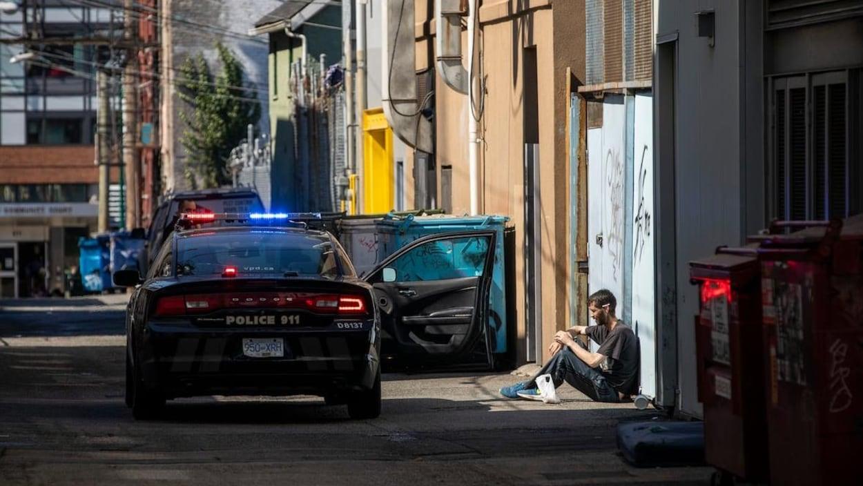 Une voiture de police dans une ruelle du quartier Downtown Eastside, de Vancouver, connu pour sa population itinérante et son épidémie de surdose,.