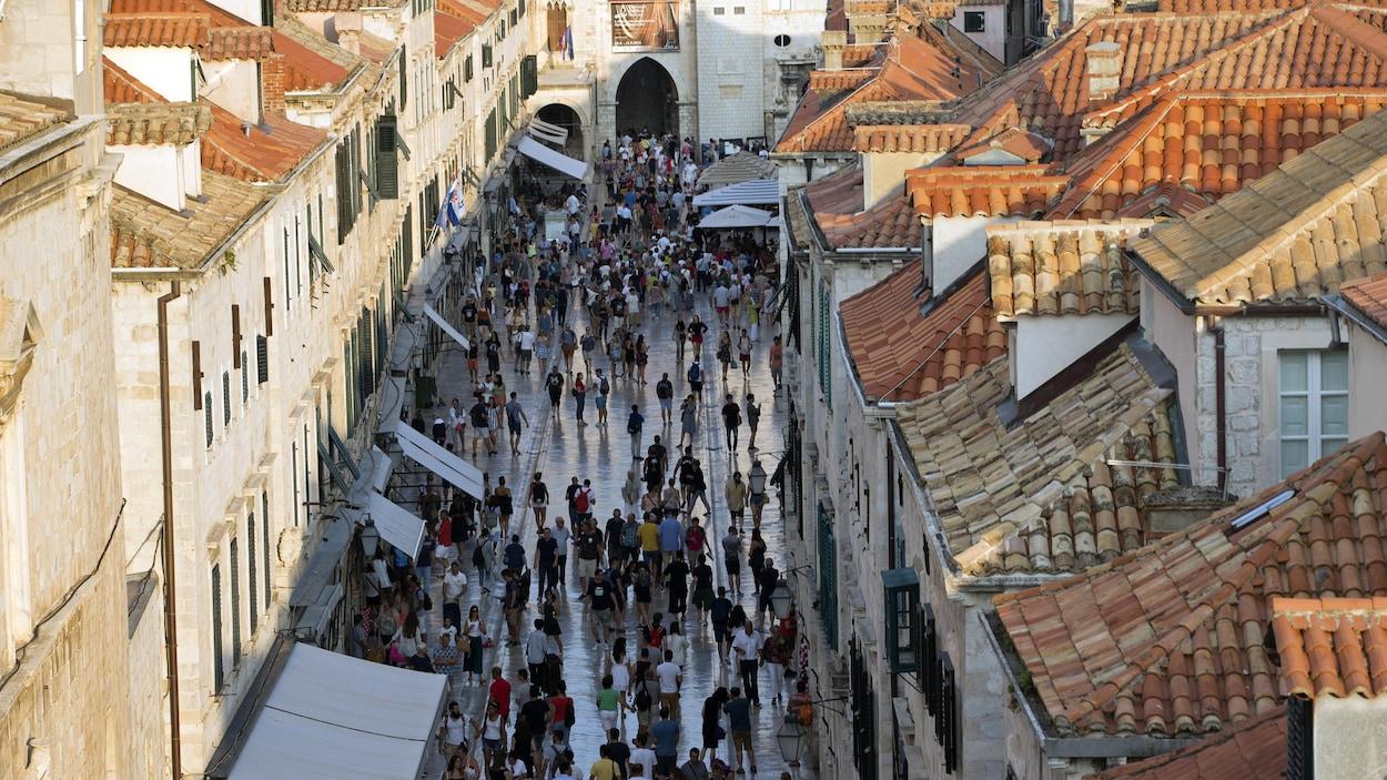 Vue en hauteur d'une rue piétonne de la vieille ville de Dubrovnik où des dizaines de touristes s'entassent.