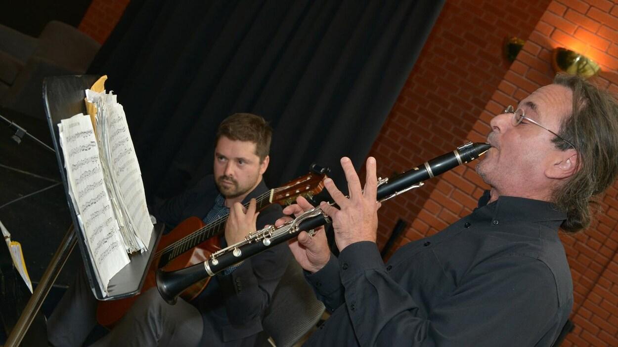 Deux hommes jouent de la musique.