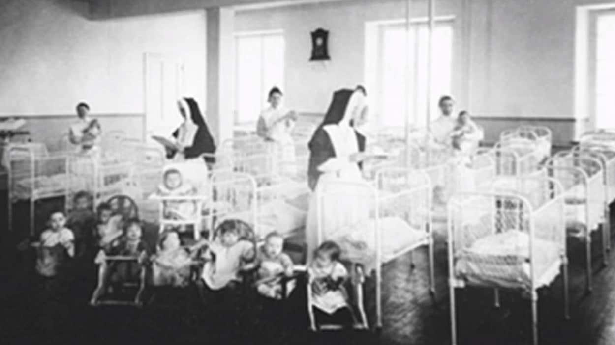 Des lits vides et des orphelins assis devant des religieuses.