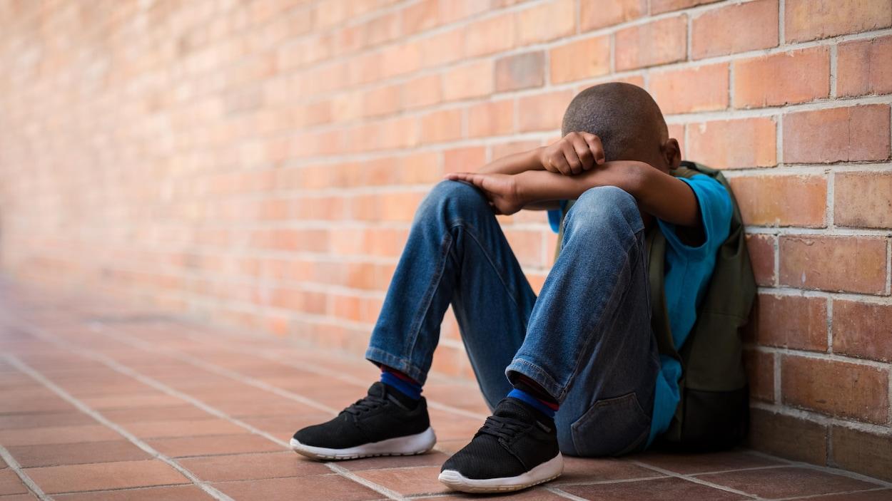 Un jeune garçon noire assis par terre, le visage caché.