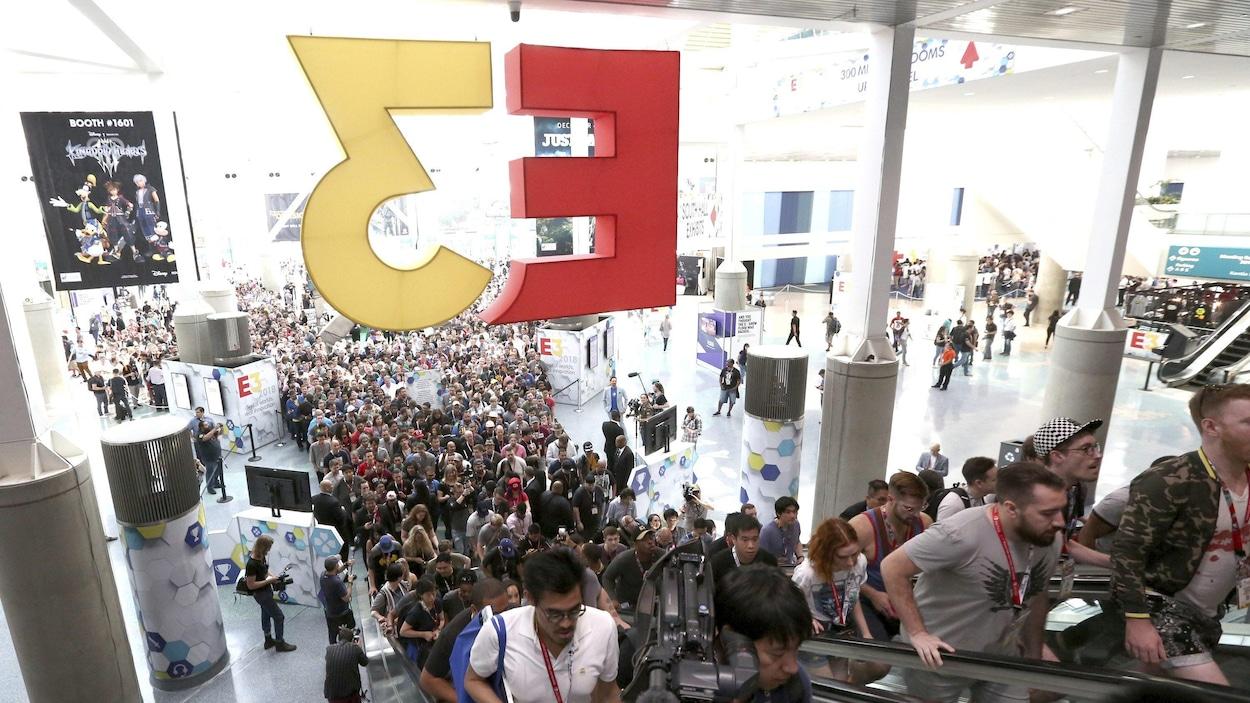 Une photo montrant des centaines de personnes faisant la queue pour gravir les escaliers roulants, dans l'entrée principale du centre des congrès de Los Angeles. Un énorme logo de l'E3 est suspendu au-dessus des escaliers roulants.