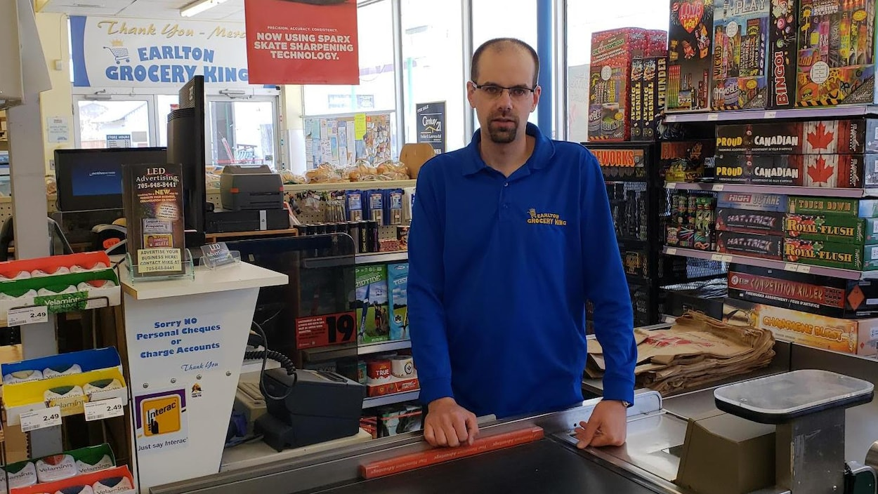 Michel Maurice, derrière la caisse, dans l'épicerie d'Earlton.