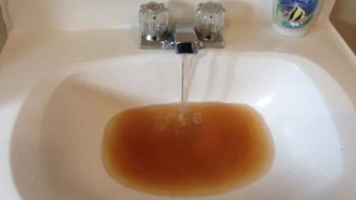 Une eau sale coule dans un lavabo