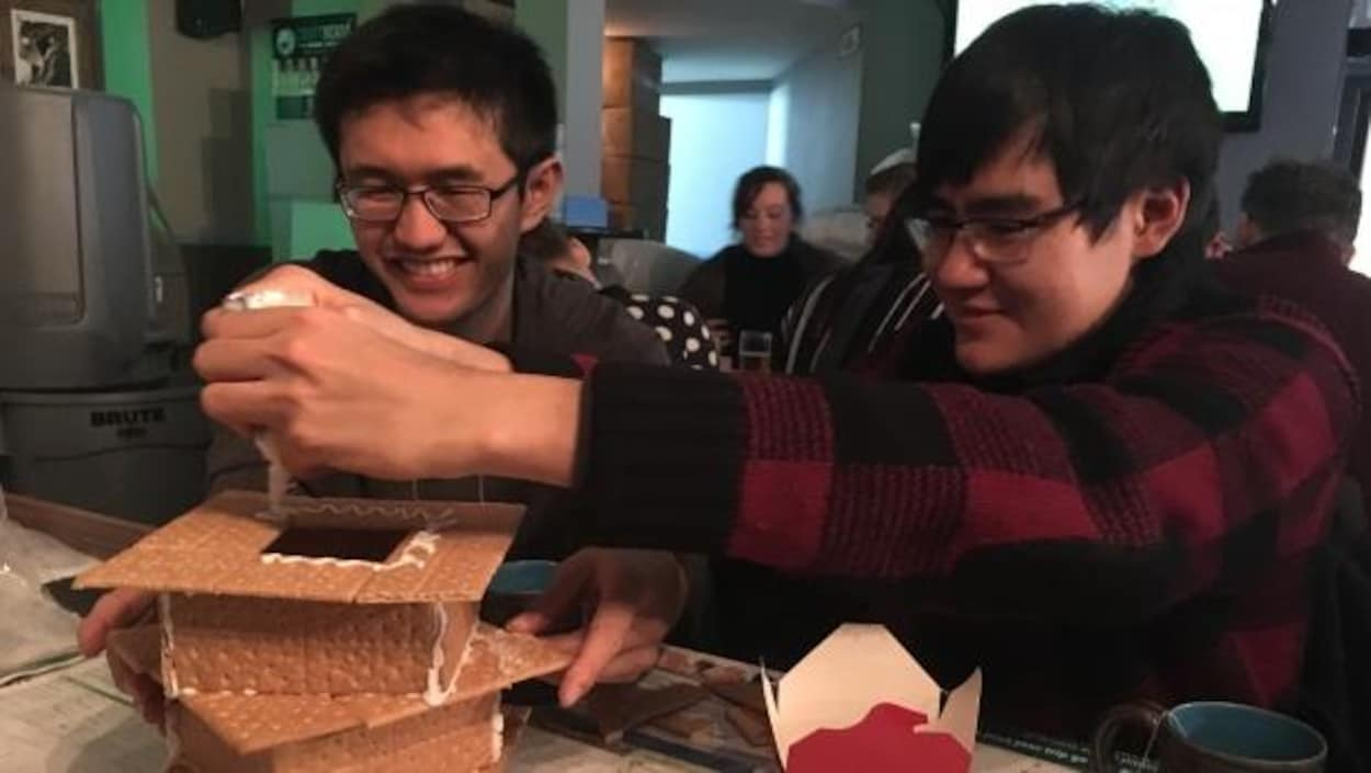 Les participants construisent une maison de pain d'épice au cours d'une récente soirée d'échanges linguistiques Loose Lips à la brasserie Craft Heads.