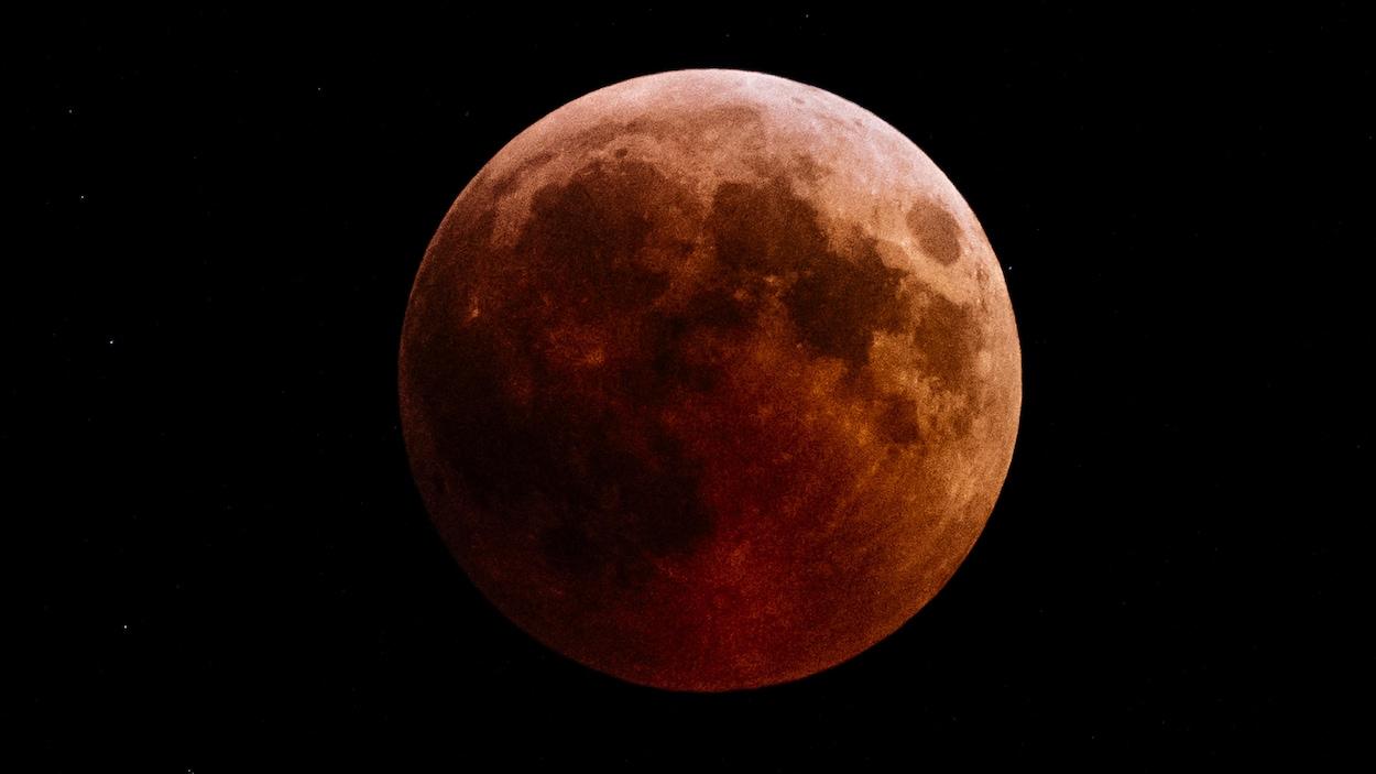 La Lune, pleine, est rougeâtre à cause de la réflexion de la lumière du Soleil par l'atmosphère terrestre.