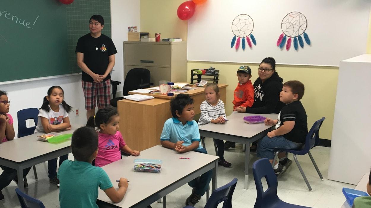 L'enseignante de maternelle est debout devant les élèves assis aux trois tables de la classe.