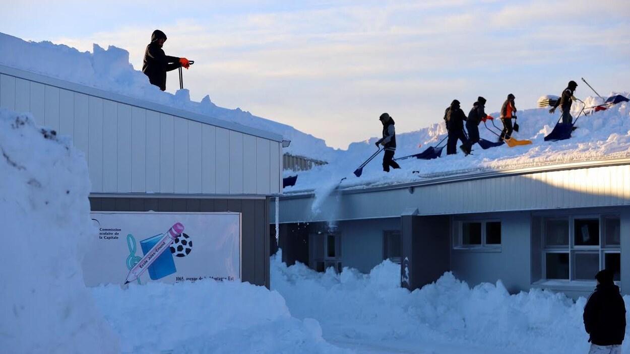 Plusieurs travailleurs s'activent sur le toit de l'école primaire Jules-Émond du secteur Val-Bélair afin que l'établissement scolaire puisse rouvrir ses portes.