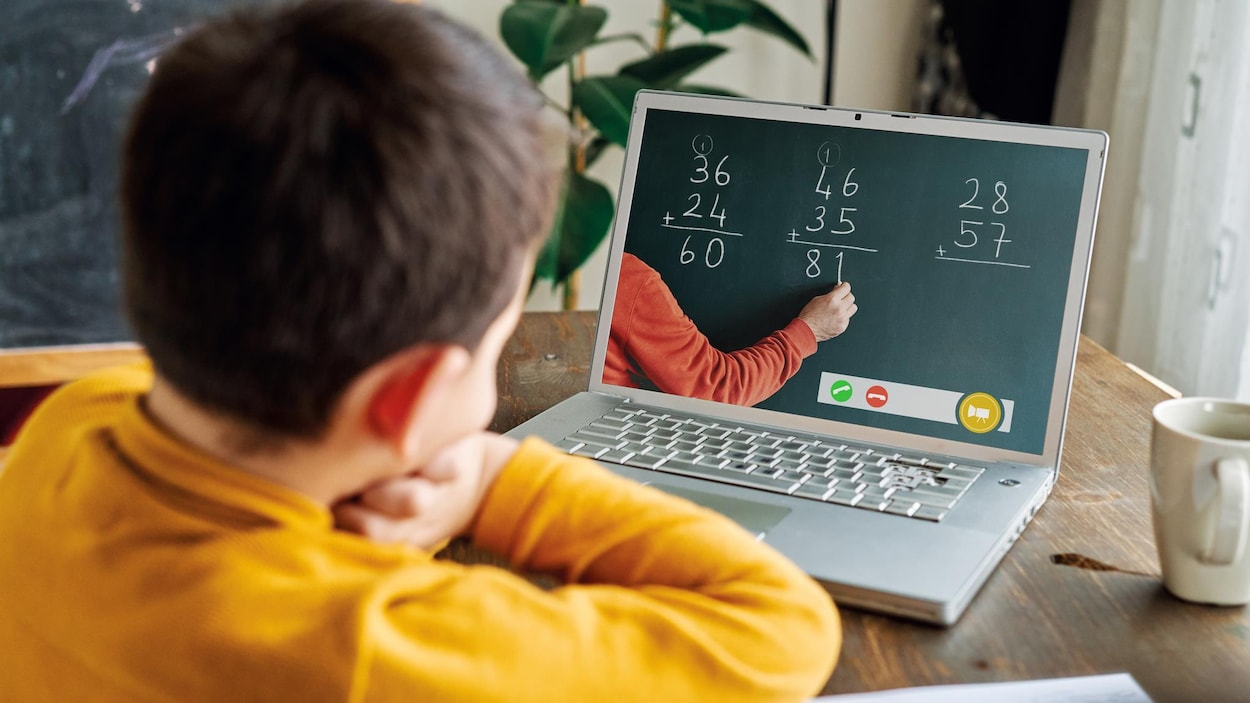 Un enfant devant un ordinateur regarde son enseignant écrire des additions au tableau.
