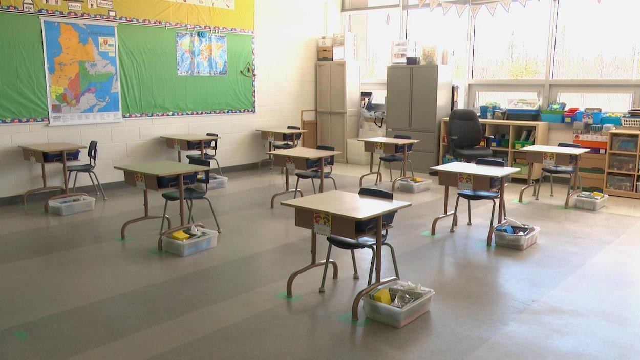 Neuf pupitres à deux mètres de distance les uns des autres dans une classe du primaire.