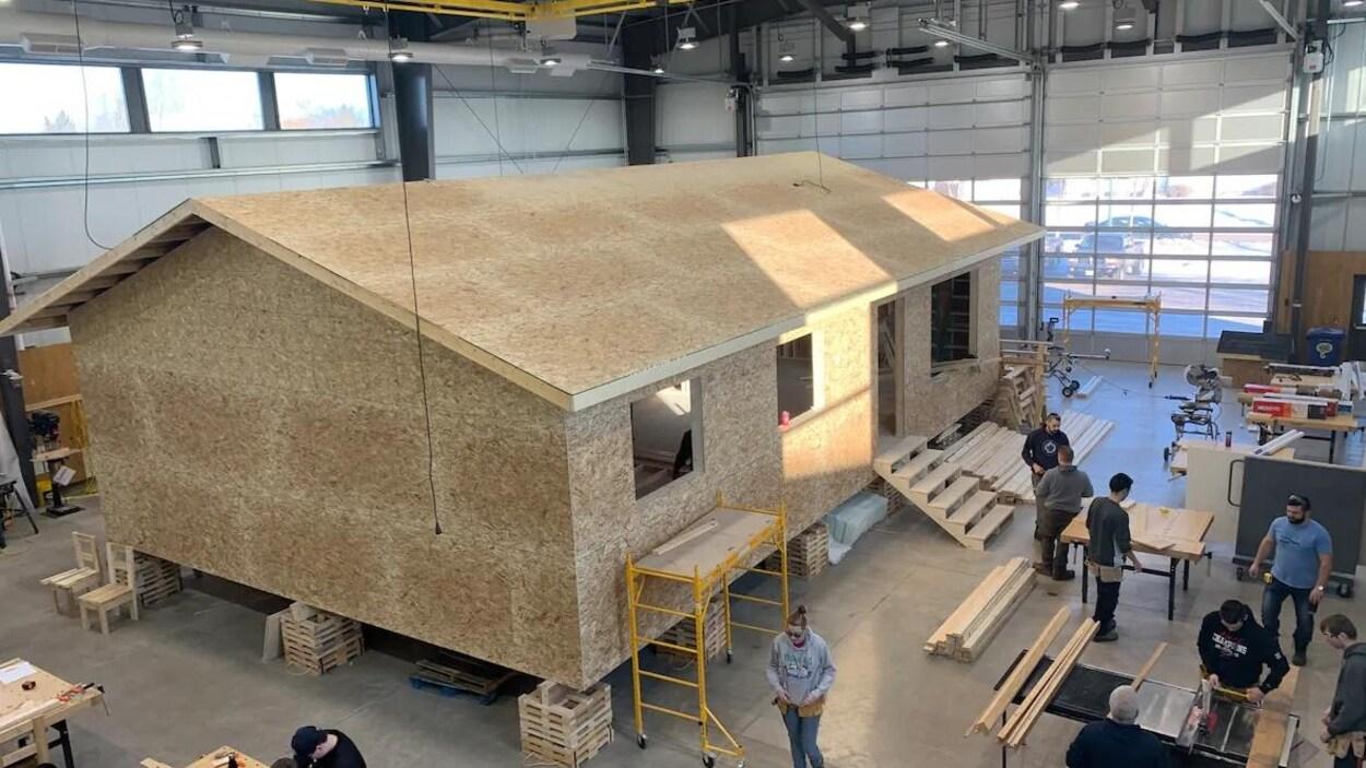Une maison en construction est dans un vaste atelier, une douzaine de personnes travaillent autour.