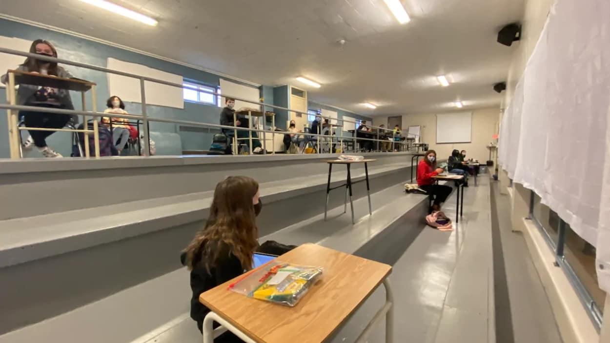 Des élèves sont assis en classe à deux mètres de distance entre eux.