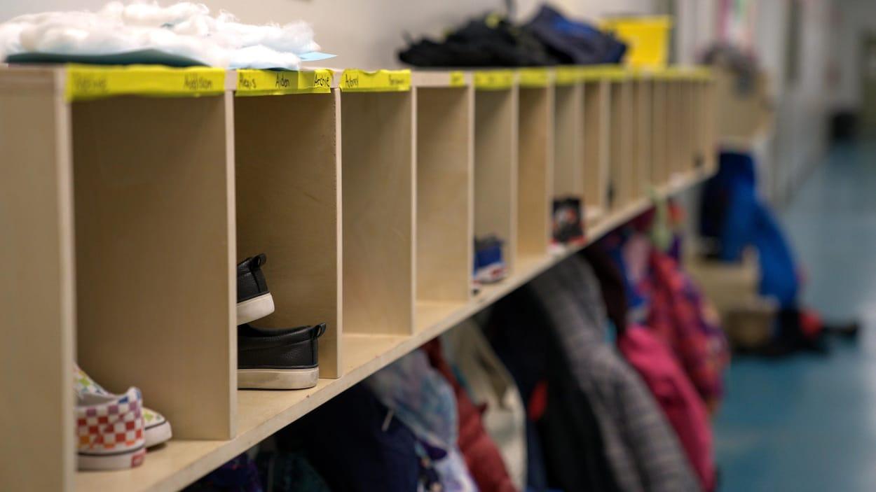 Des chaussures et des manteaux sont rangés le long du mur dans le couloir d'une école.