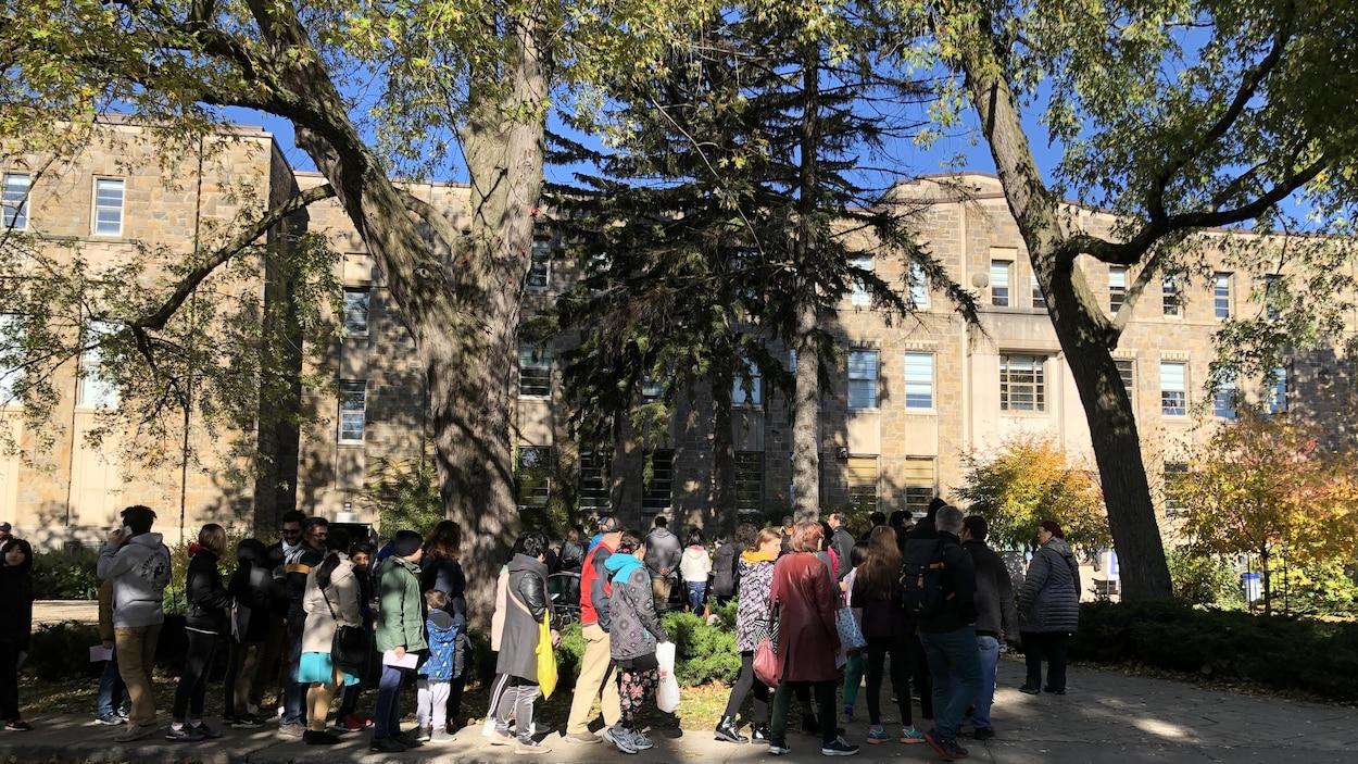 Une file d'élèves et de parents devant un établissement.