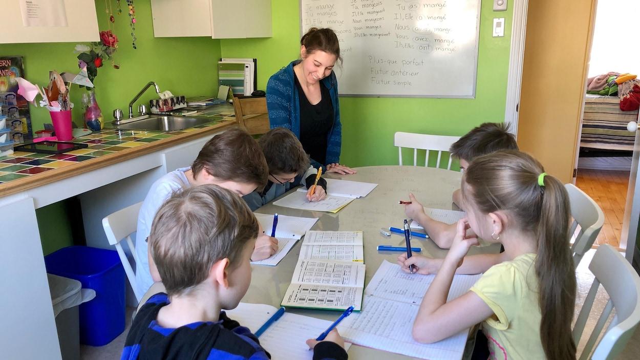 Une enseignante supervise de jeunes élèves qui travaillent sur la table de la cuisine.