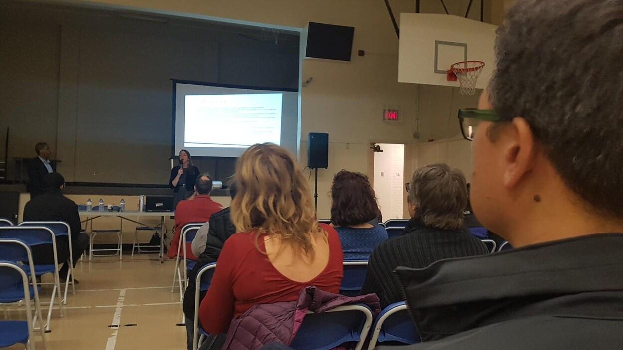 Des parents sont assis sur des chaises bleues dans un gymnase. Ils regardent une présentation.