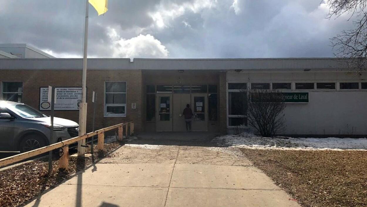 Le devant d'une école avec le drapeau fransaskois jaune et vert.