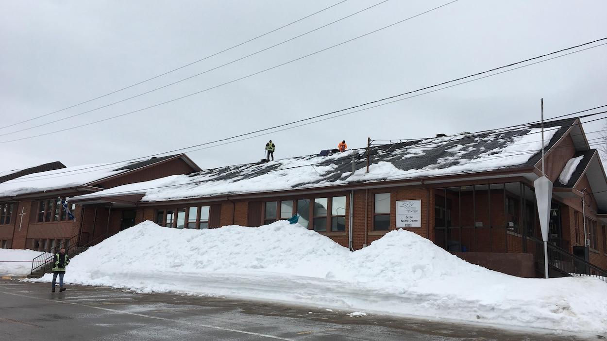 Des déneigeurs sont à l'oeuvre sur le toit de l'école.