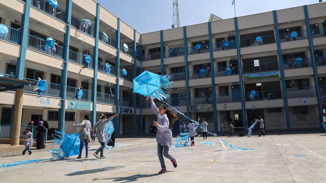 De jeunes filles s'amusent avec des articles promotionnels de l'UNRWA dans une cour d'école.