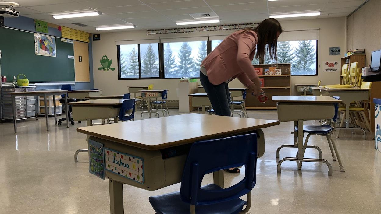 Une enseignante de l'école Les Sittelles, de Saint-Georges, dans sa classe. Les pupitres des élèves sont très espacés les uns des autres.