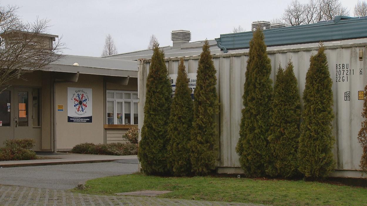 L'entrée de l'école vue de l'extérieur, avec le logo de l'école, et une partie d'un bâtiment un peu désuet avec quelques arbres devant.